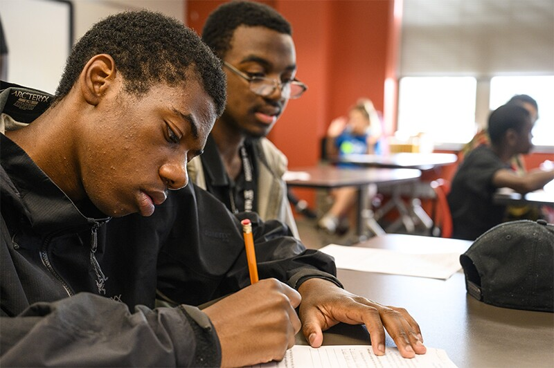 Two students working on an assignment at a desk.