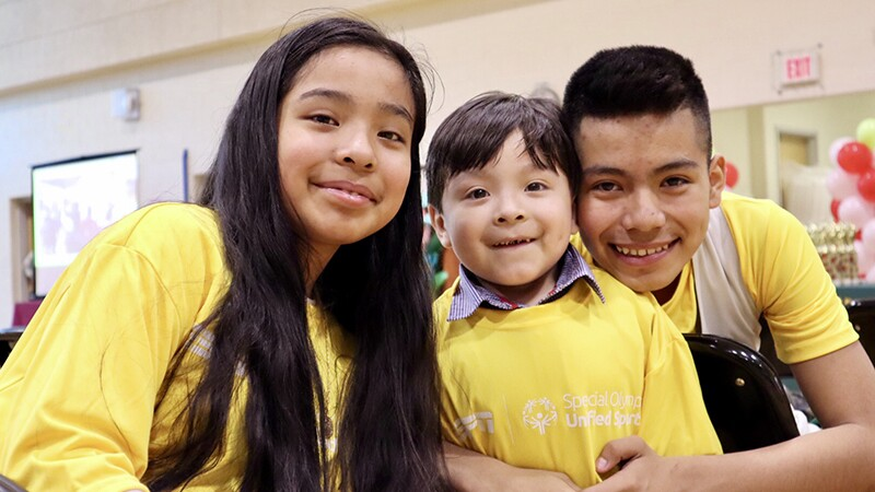 Young boy and two young adults have on yellow Unified Sports t-shirts.