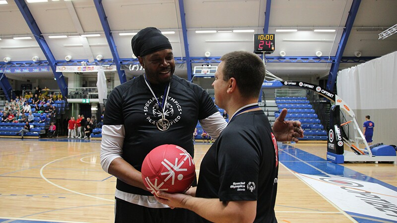 NBA legend Sam Perkins presents Prime Minister of Estonia Jüri Ratas with a Special Olympics basketball on the sidelines of the court.