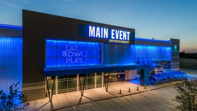 Photo of Main Event Entertainment building lit up in blue lights at dusk. The sign on the outside wall reads: Eat. Bowl. Play.
