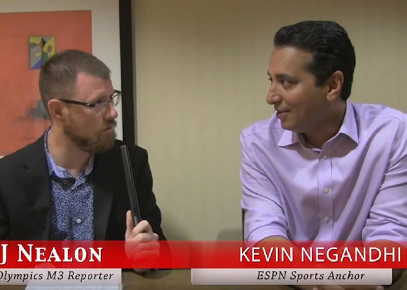 RJ Nealon interviewing Kevin Negandhi; both are sitting down at a table.