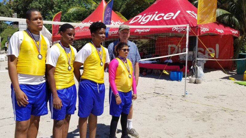 Four volleyball medalists (three boys and one girl) are joined by Aldis Berzins, 1984 Olympic volleyball gold medalist, on the beach in front of a volleyball net.
