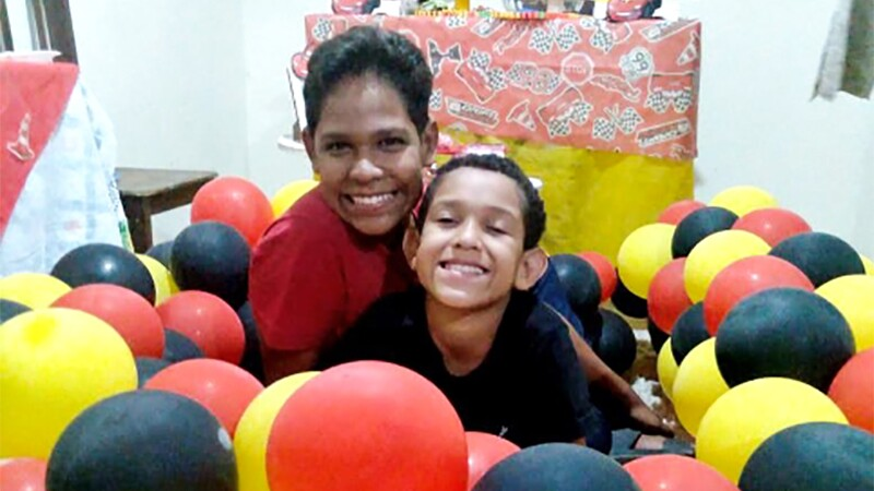 """Two young boys with big smiles sit on the ground hugging, surrounded by a circle of red, yellow, and black balloons. In the background is Disney's """"Cars""""-themed decorations."""
