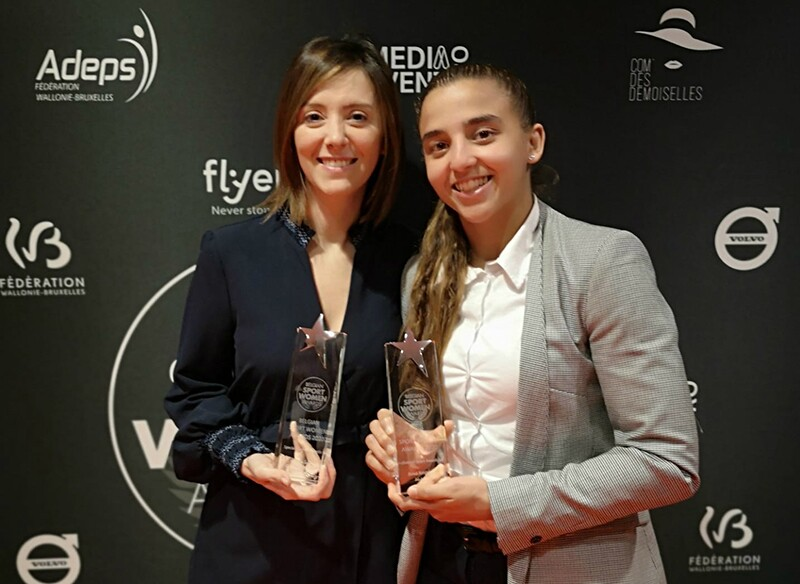 Two young women holding awards.