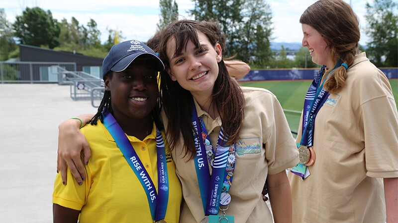 Novie poses alongside one of her competitors. They both have medals around their necks.