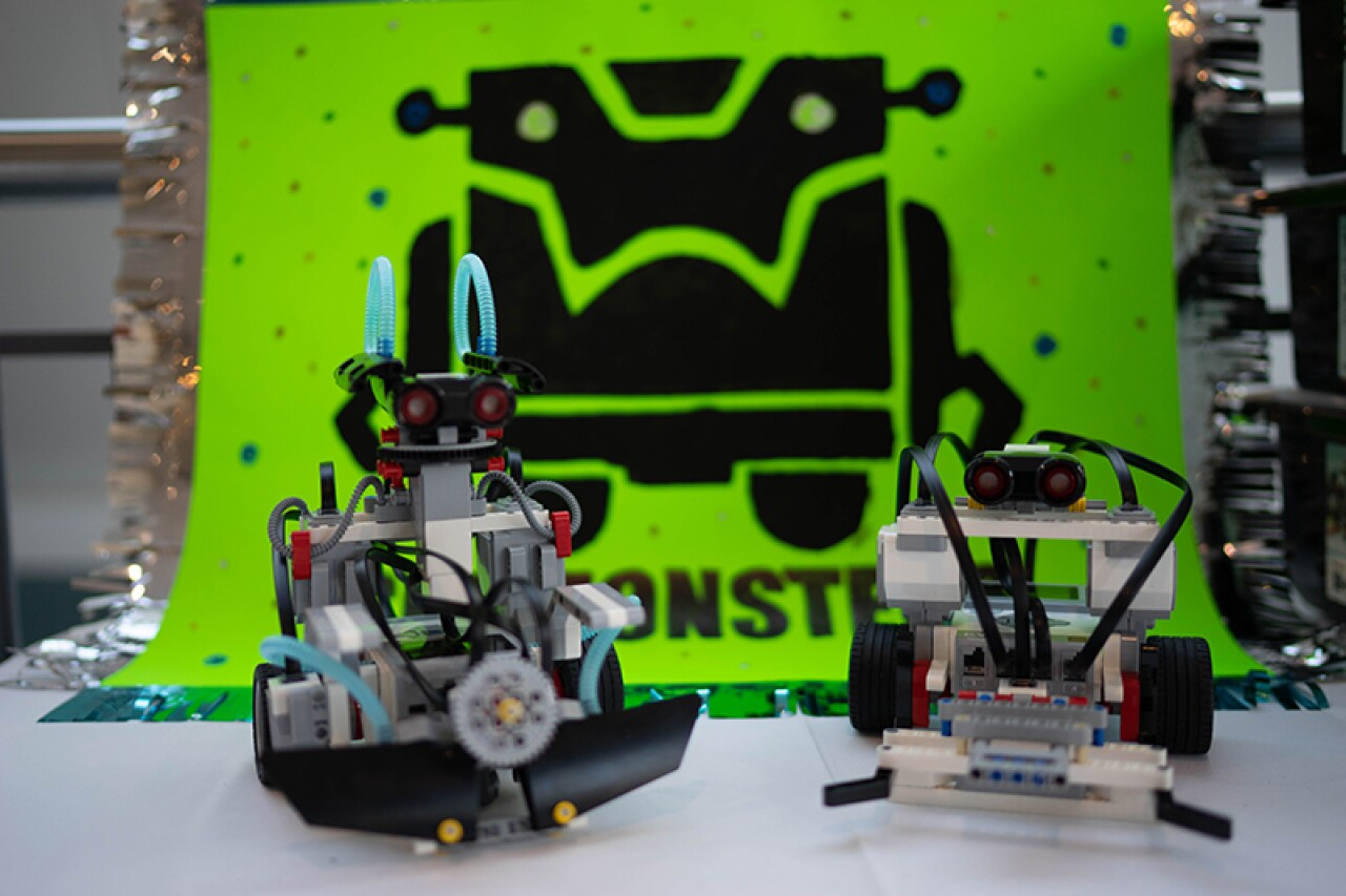 Two robots sitting in front of a logo that is an illustration of a robot with text blow that reads, Monster