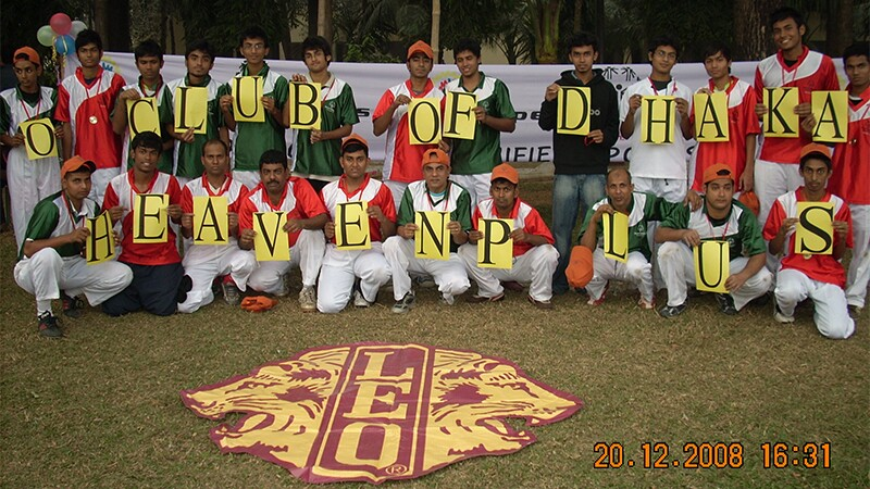 """Two rows of people the back row standing and the front row crouching hold up individual up letters that spell out """"O Club of Dhaka Heaven Plus"""""""