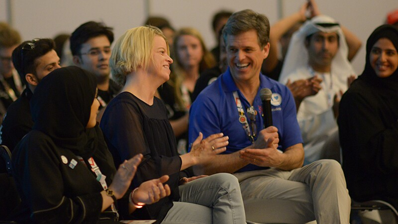 Youth Leaders from Around the World - Daina Shilts talking with Tim Shriver, both are sitting down and spectators are watching.