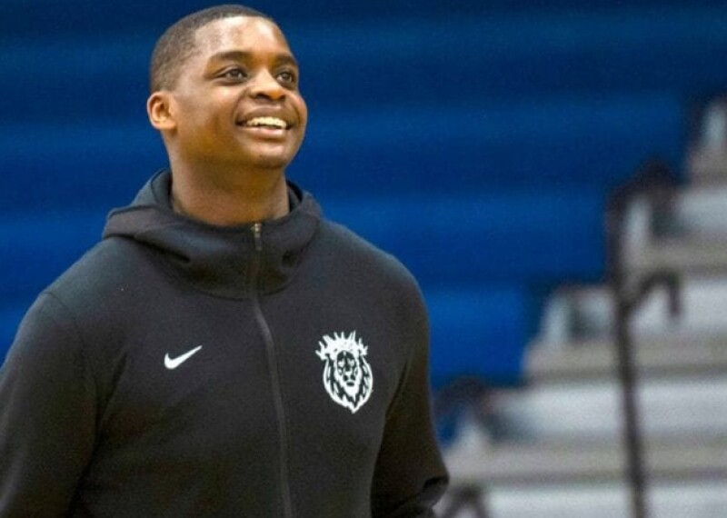 Kalin Bennett standing in the gymnasium looking off into the distance with a smile on his face. He's in a black Nike hoodie; blue bleachers and stairs are in the background.