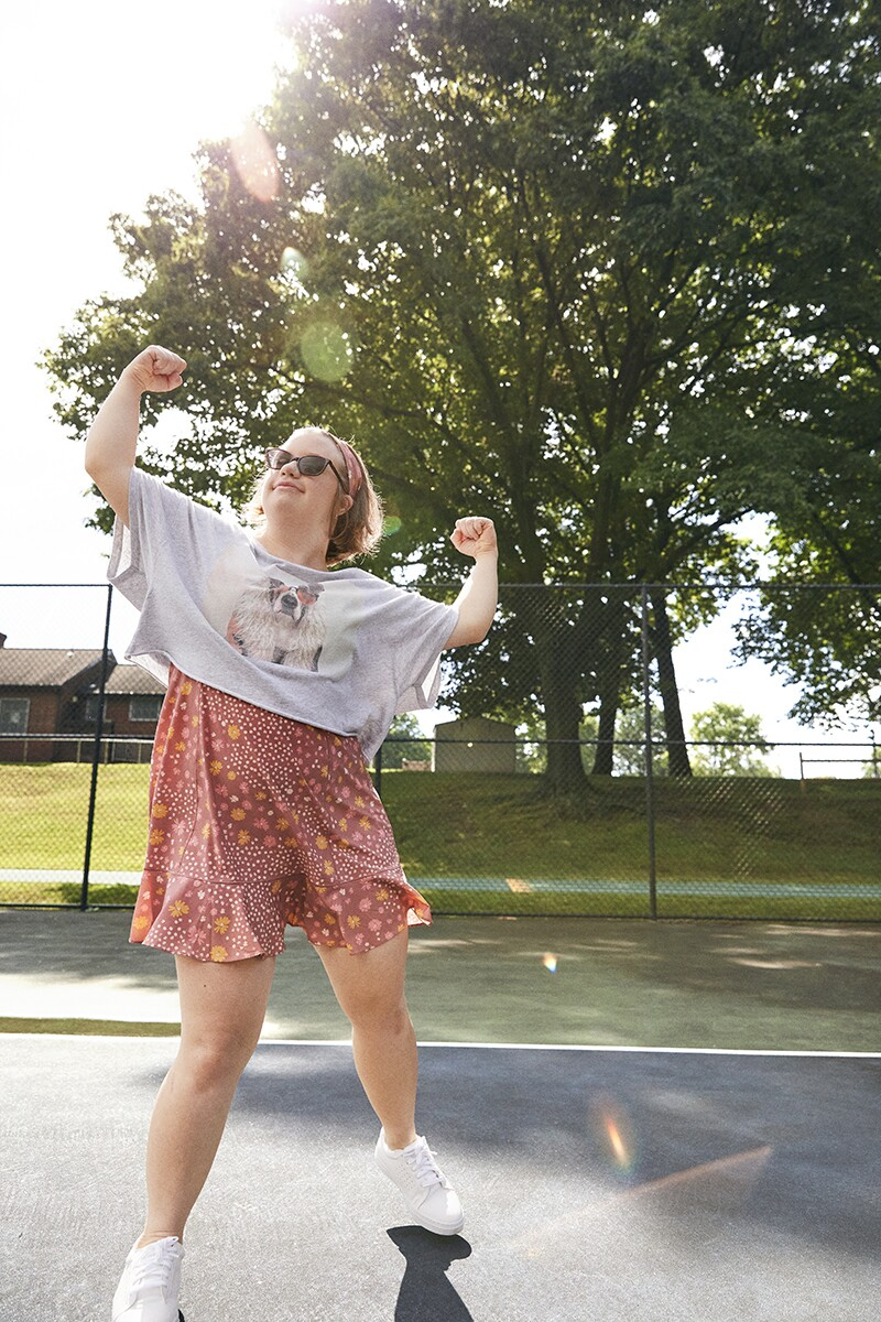 Megan shows off her muscles on a tennis court wearing a cropped shirt over a short dress.