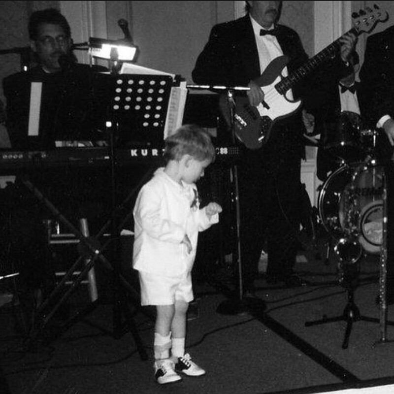 A photo of young RJ pretending to be a rockstar at his aunt's wedding.