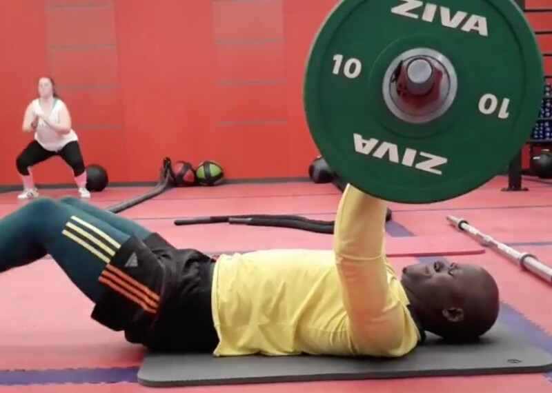 Banele laying on the ground in a gym doing chest presses.