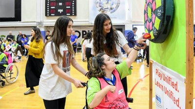 In a crowded gym, two girls guide the hands of another girl in a wheel chair, as she places a Velcro ball onto a target.