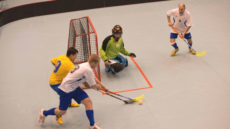 Athlete attempting to make a goal while his opponent blocks; the goalie and another player watch.