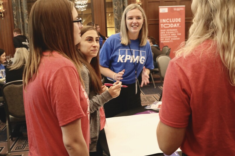 Employee from KPMG engaging in conversation with youth leaders from Special Olympics Canada