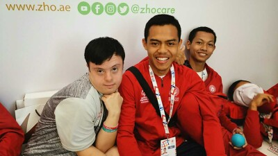 Four young men sitting in a group, two have on long sleep red Special Olympics Abu Dhabi 2019 pull overs.