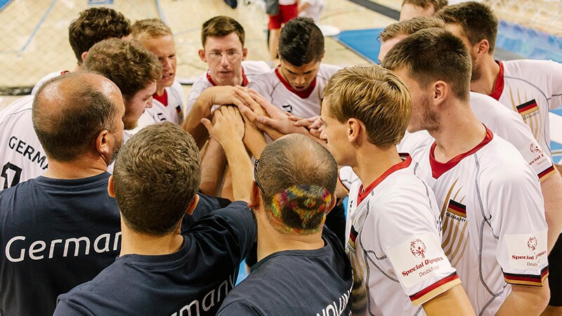 A group of players and coaches standing in a circle with their hands in the middle in a team huddle.