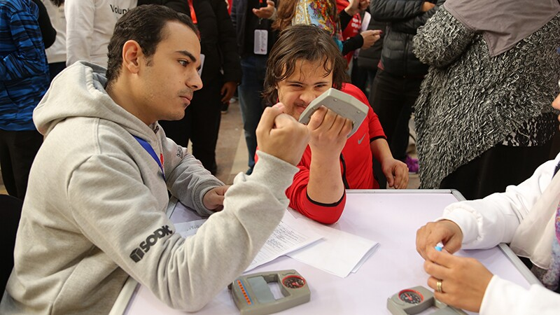 Young Athlete squeezes a device while a professional observes.