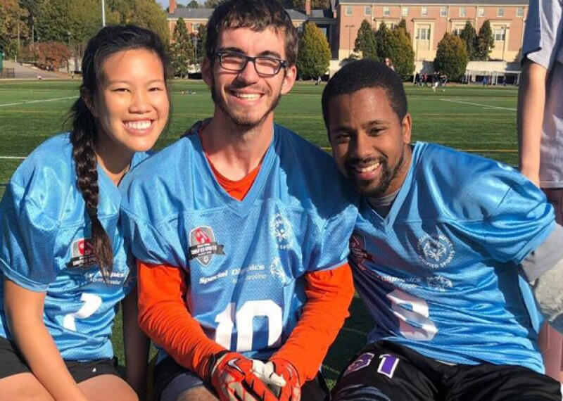 Three college students in blue jerseys sitting side by side and smiling for a group photo.