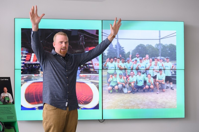 A Special Olympics athlete speaks in front of a screen showing pictures of him.