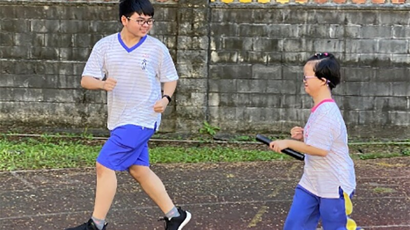 A boy and girl look at each other smiling as they run down an outdoor track. The girl holds a baton, and they both wear school uniforms.
