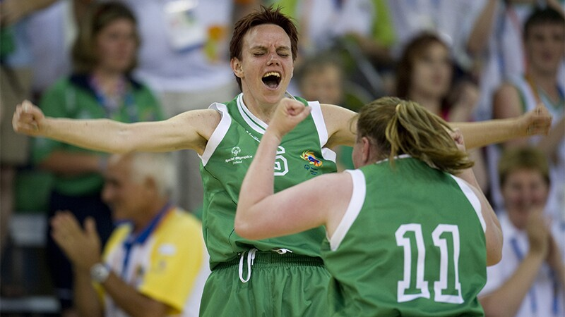 Celebration between two female athletes, both in green uniforms.