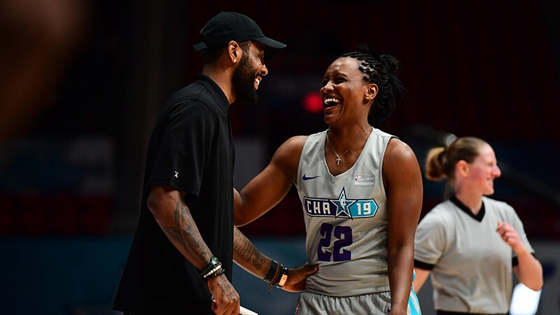 Coach Kyrie Irving shares a laugh with WNBA player Ashley Battle a ref. can be seen in the background.