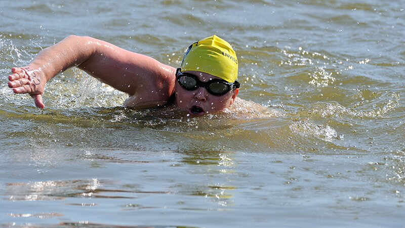 Athlete in a yellow swim cap focuses on his strokes.