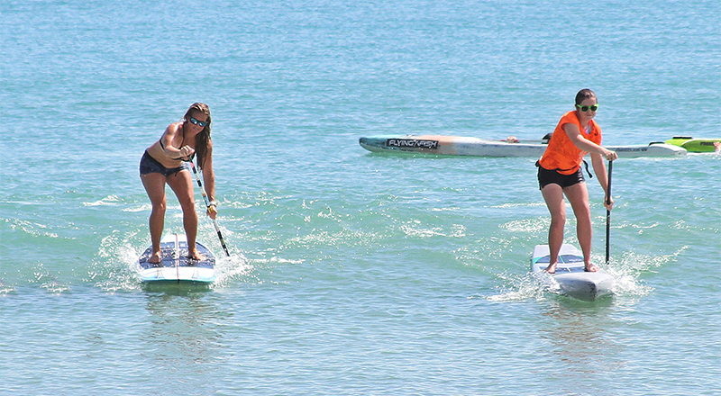Two women stand up paddleboard in the ocean.