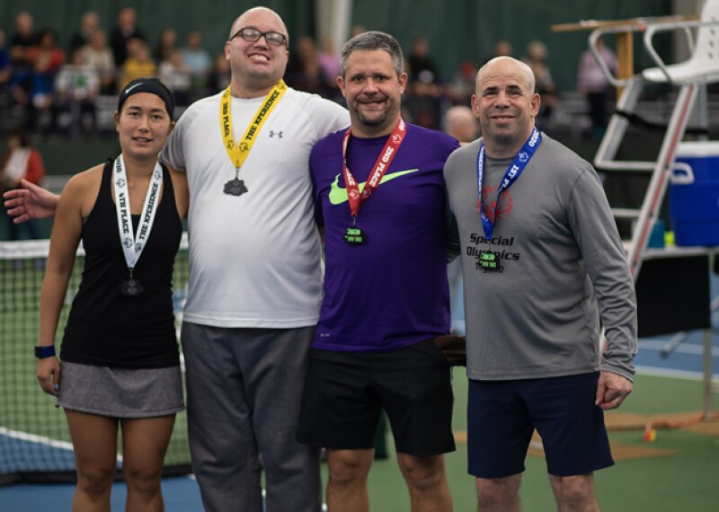 Four athletes stand side by side in a group in front of a tennis net