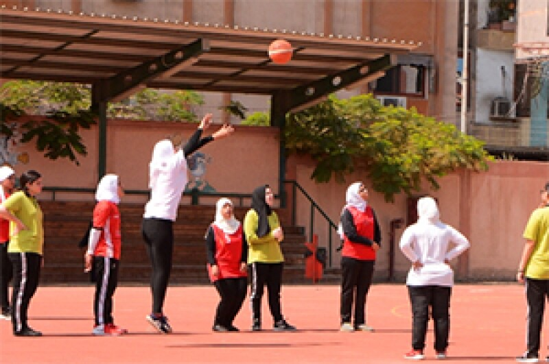 A girl is mid-basketball shot as 8 other girls look on at an outdoor basketball court. They all wear Special Olympics jerseys.