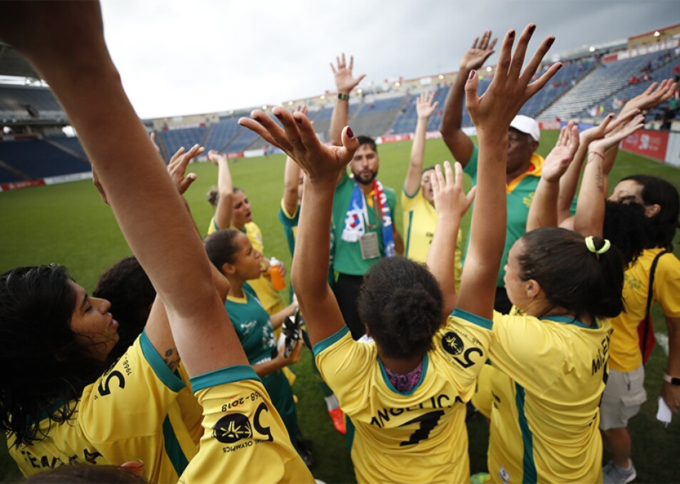 Athletes on a field huddled into a circle cheering with their hands up.