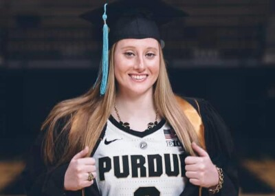 Abby in a graduation cap and gown with a Purdue jersey under.