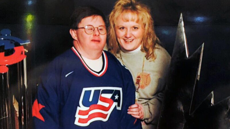 Kevin O'Brien on the left wearing a blue USA sports Jersey. Sister, Melanie, sits behind him slightly holding his left arm with her left hand. Both are smiling.