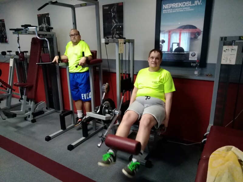 Two Special Olympics athletes using equipment in a gym.
