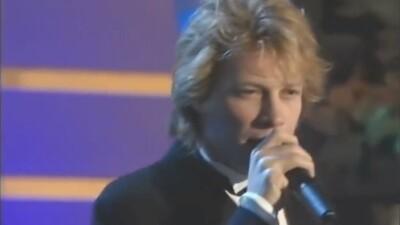 Jon Bon Jovi dressed up in a tuxedo singing on stage.