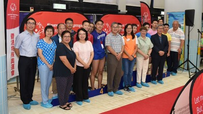 Participants, athletes, parents and representatives of the 42nd Special Olympics Hong Kong Swimming Competition stand in a row shoulder to shoulder in front of Special Olympics signage.