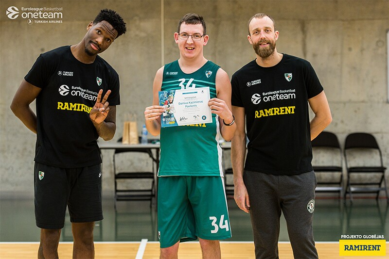 An athlete holding an certificate with other players standing on either side of him in a gymnasium.