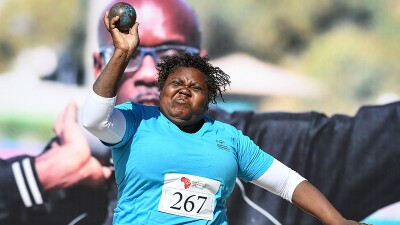 Shot put athlete shot putting on the field.