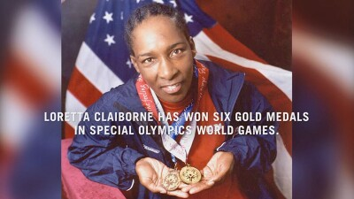 Loretta Claiborne holding her gold medals in front of the American flag.