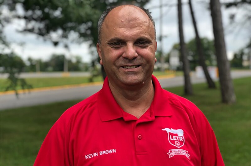 Kevin Brown standing outside in a red LETR polo shirt.