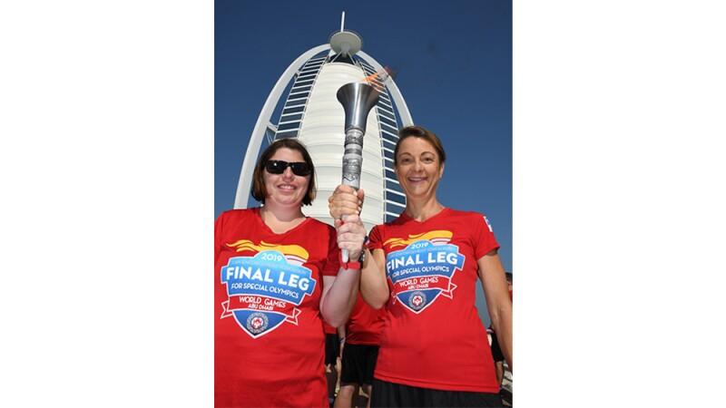 Sherrie holds the torch alongside a law enforcement officer in front of the Burj Al Arab building in Dubai.
