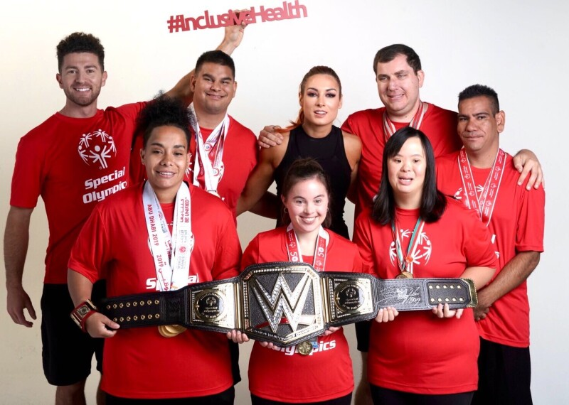 Group of athletes standing together holding the WWE championship belt