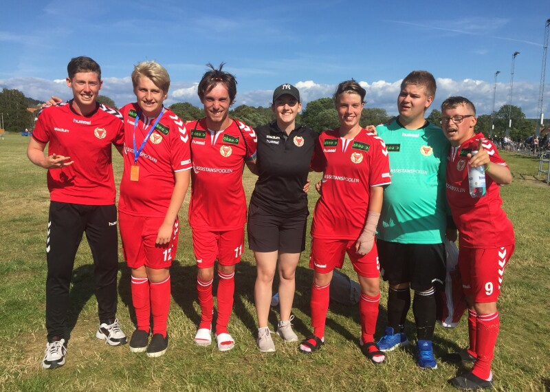 A group in red football kits stand on a football pitch with their arms around each other facing the camera smiling.