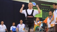 weight lifter celebrating as referees watch.