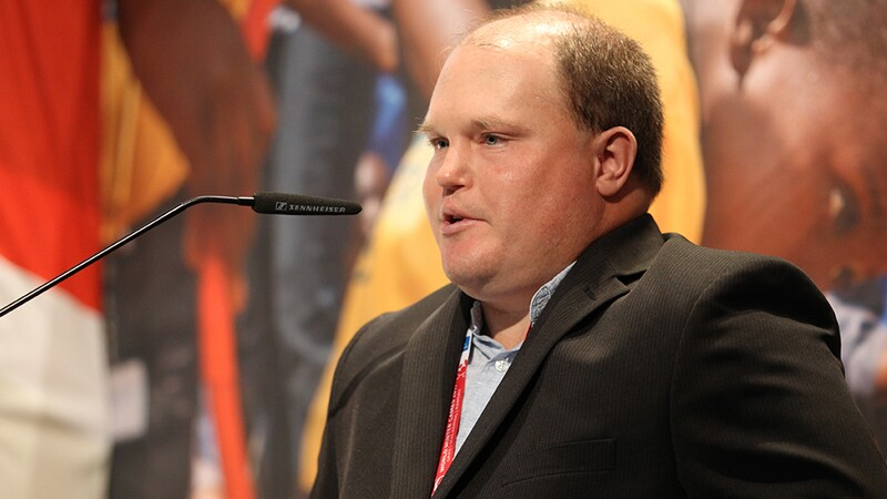 Close up of Ben Haack, in a suit jacket, speaking into a microphone.