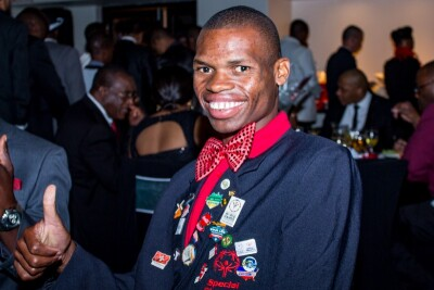Nyasha Derera sitting at a formal event wearing a dinner jacket, red bow tie, and inspirational pins on his lapel. He's smiling and giving a thumbs up.