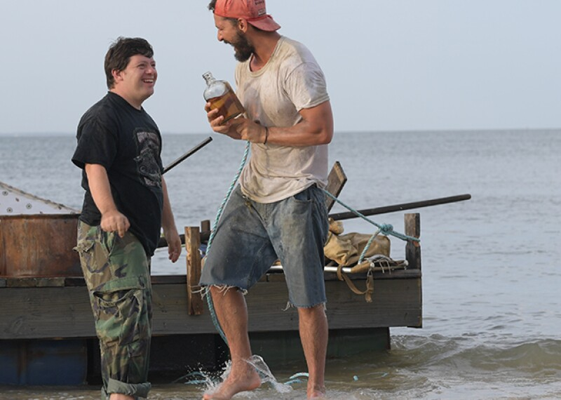 Zack and Shia standing in the water (up to their ankles) next to a small boat.