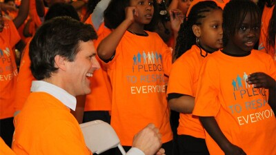Tim Shriver at a school with young children. Everyone is wearing an orange shirt that reads: I Pledge to respect everyone.