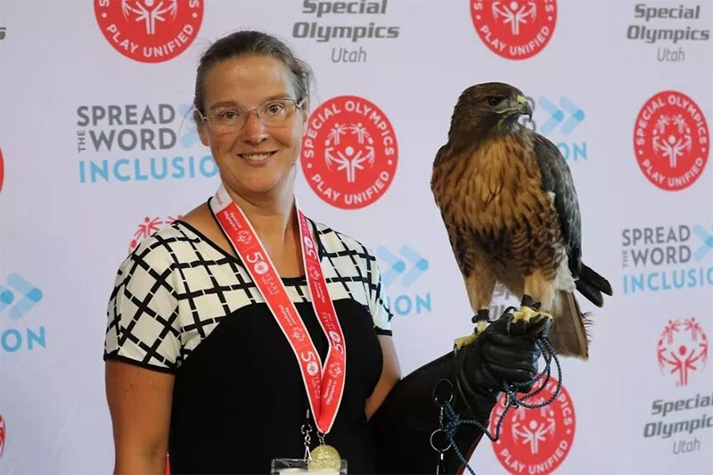 Amber standing for a picture with her red tail hawk